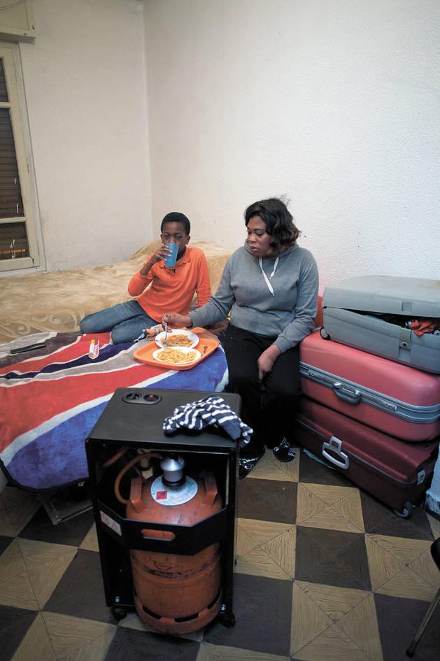 Philomena, de 42 años, y su hijo Nicolás, de 7, cenan sobre la cama de la habitación donde viven desde hace un año en Pamplona y por la que pagan 220 euros al mes.
