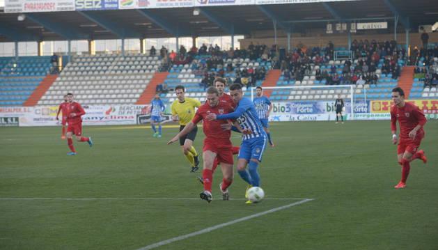 Sam Piette (Izarra) lucha por el balón contra un rival de la Ponferradina durante el encuentro de ayer en El Toralín.
