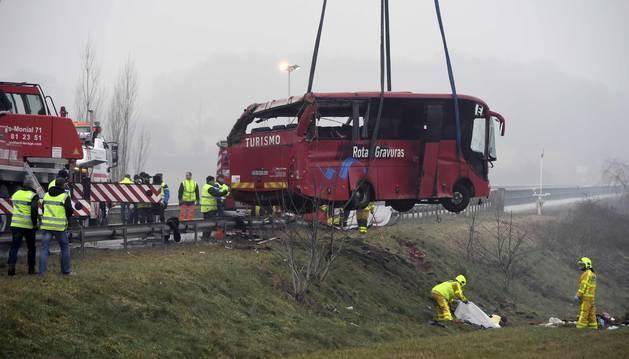 Varios equipos de bomberos retiran el autobus accidentado de la carretera.