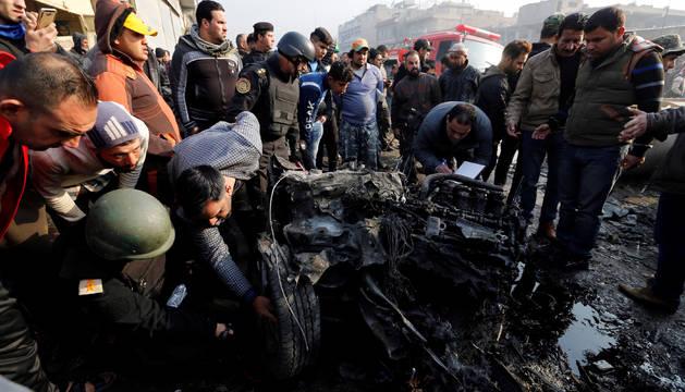 Varias personas inspeccionan el coche bomba que ha explotado en Bagdad.
