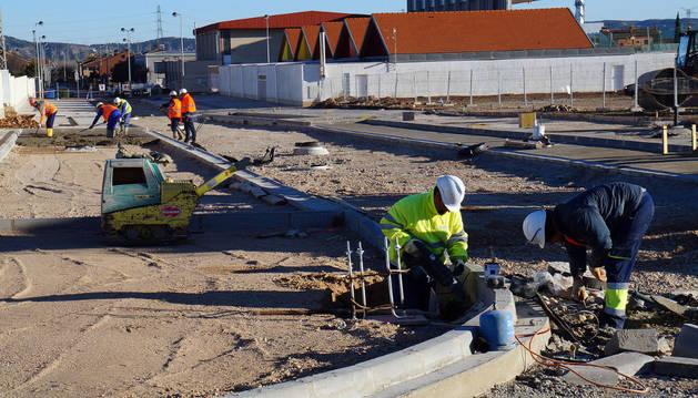 Varios operarios trabajan en las obras de urbanización de la parcela donde se construirá el instituto.
