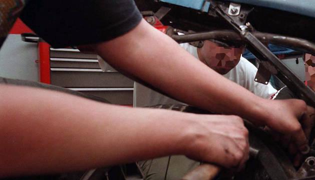 Jóvenes mecánicos trabajan en el arreglo de una moto.