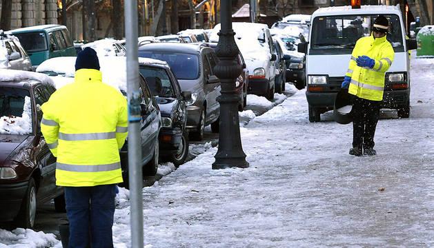 Un empleado municipal esparce sal para evitar el hielo tras una nevada en Pamplona.