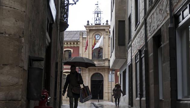 Dos personas caminan por la calleja de los Gaiteros, con la fachada municipal al fondo.