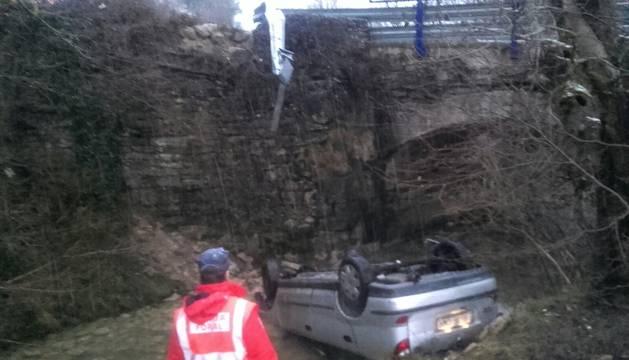El coche ha quedado boca abajo tras caer al río.