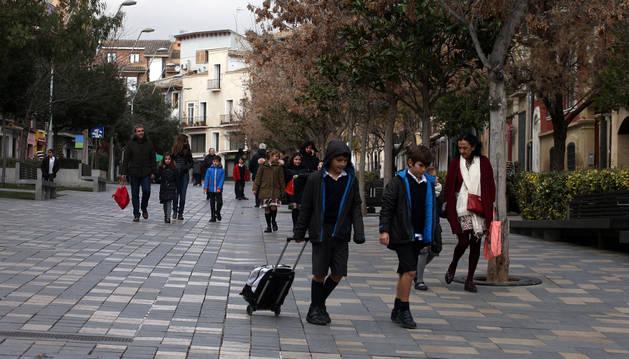 Varios niños, acompañados por adultos, caminan por la céntrica calle Herrerías de la capital ribera.