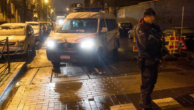 Un oficial de policía se encuentra junto a una furgoneta durante las búsquedas en la calle Delaunoy en Molenbeek