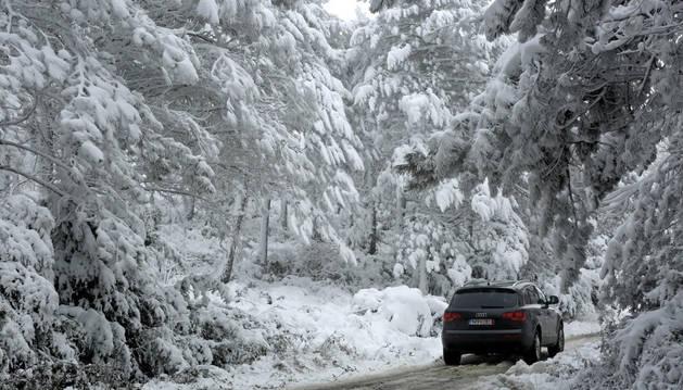 Imagen de un coche que circula entre la nieve por el Alto de El Perdón
