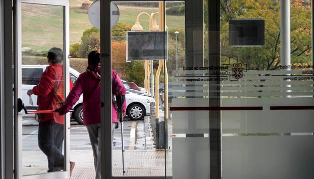 Dos personas salen por una de las puertas del edificio de consultas del hospital García Orcoyen.