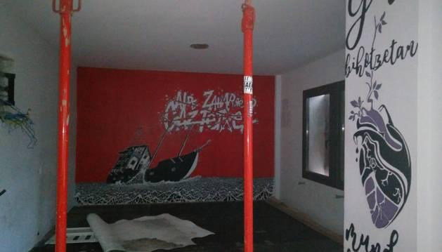 Una de las salas de la planta baja del chalé, apuntalada, y con pintadas alusivas al gaztetxe del Casco Antiguo.