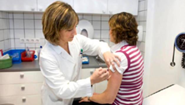 Una persona es vacunada por una profesional.