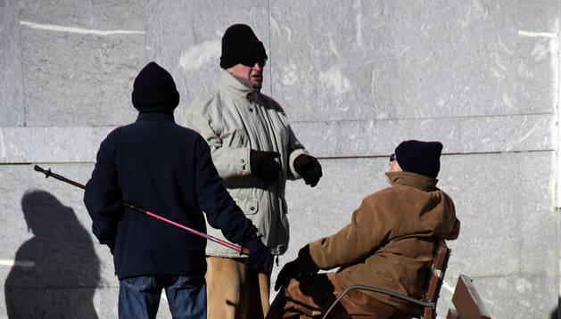 Tres hombres se protegen del frío ayer en el parque de Yamaguchi.