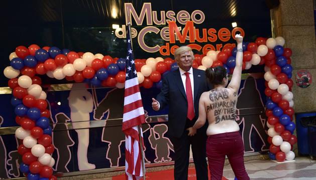 Una activista de FEMEN enseña sus pechos a la figura de cera de Trump.