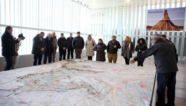 Los asistentes a la visita al centro de Aguilares contemplan una gran maqueta de Bardenas en relieve.