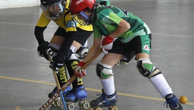 Dos jugadores pugnan por controlar la pelota durante un encuentro de Juegos Deportivos de Navarra entre Lagunak e Ikastola San Fermín  .