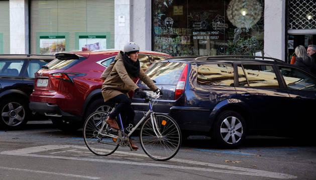 Una mujer se desplaza en bicicleta por el carril derecho de la calzada.