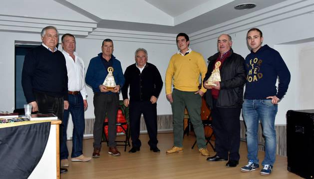 Imagen de los ganadores, con sus trofeos, entre organizadores y participantes en el acto.