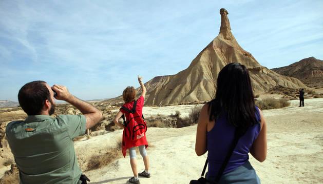 Varios turistas observan el cabezo de Castildetierra, uno de los puntos más visitados del Parque Natural de Bardenas Reales.