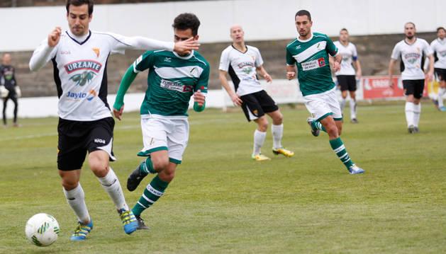 Íñigo Ros conduce el balón ante la presión de un jugador del Coruxo y la atenta mirada del resto de futbolistas del partido.