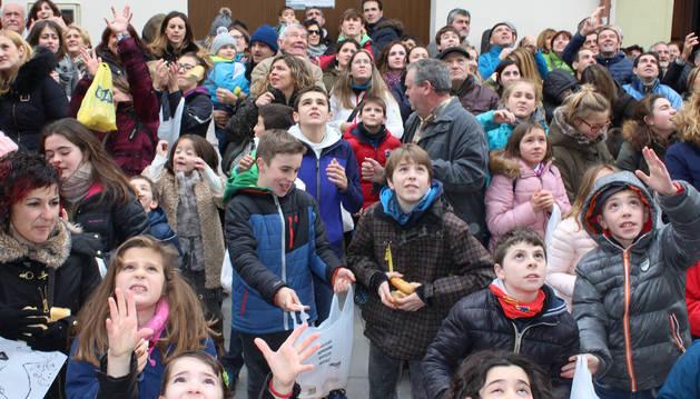 Vecinos con brazos y miradas a lo alto esperando que llegue la lluvia de panes en los bajos de la casa consistorial de Los Arcos.