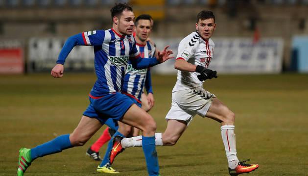 Óscar Loza, jugador del Izarra, se marcha con el balón de un rival. El futbolista del cuadro estellés fue expulsado en el partido de ayer.