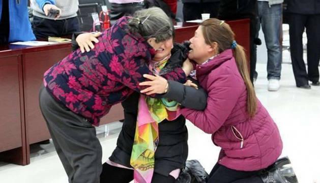 Huang Ruixiu y Huang Ruixiang, hoy de 42 y 48 años, abrazadas y emocionadas junto a su madre, Chen Jiaxiang, de 72.