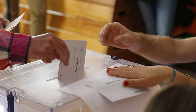 Un hombre introduce su voto en una urna durante las elecciones generales.