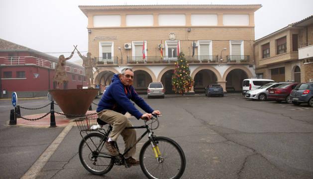 Un vecino circula en bicicleta ante la fachada de la Casa Consistorial de Cortes.