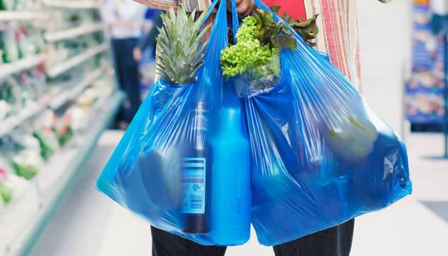 Una persona lleva dos bolsas de plástico en la mano en un establecimiento. Desde 2018 todos los comercios deberán cobrarlas.