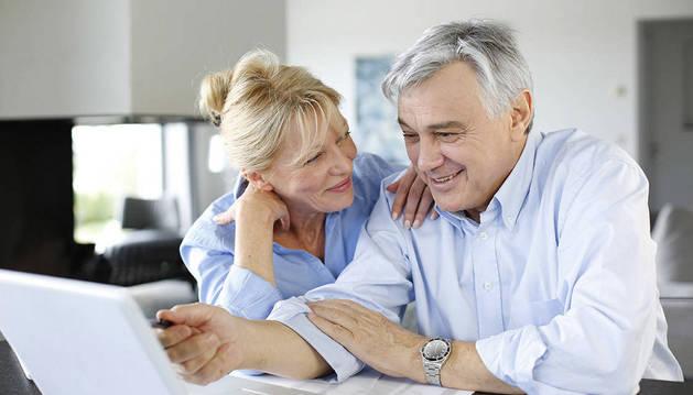 Una  pareja  en edades próximas a la jubilación realiza consulta en el ordenador.