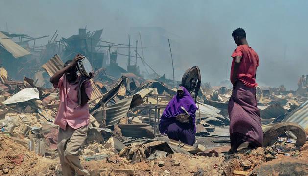 Varias personas tras un incendio en Mogadiscio (Somalia).