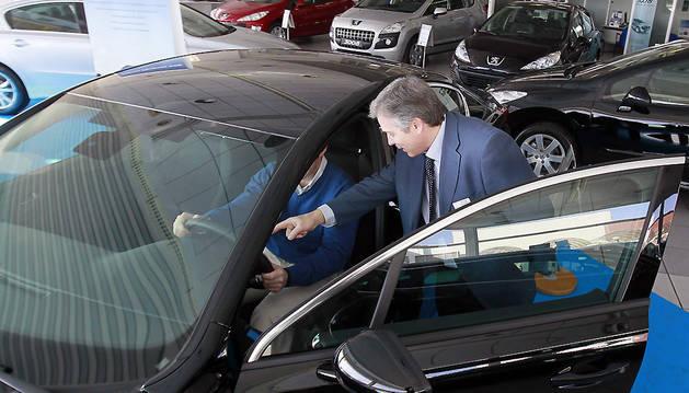 Un comercial enseña uno de los vehículos de exposición a un cliente.