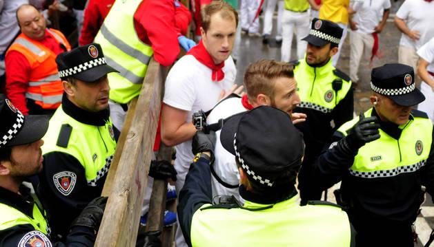La Policía Municipal retira la cámara a un corredor después del encierro.