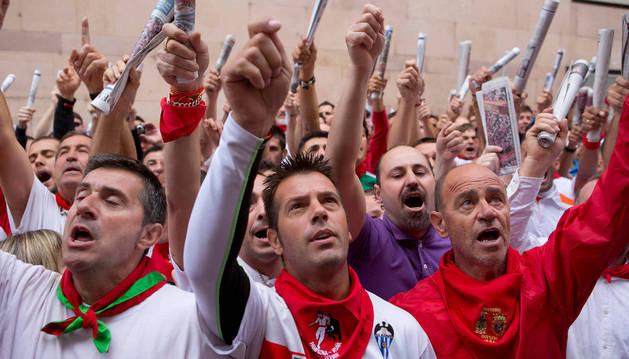 Varios corredores cantan a San Fermín antes del encierro.