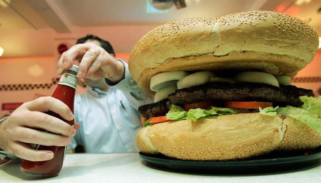 Imagen de una mujer comiendo una hamburguesa.