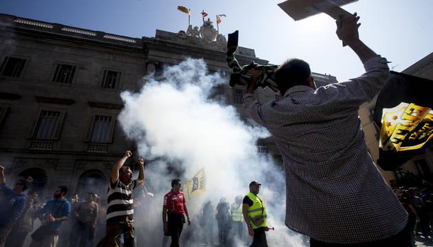 Varios taxistas, de los miles que han participado, celebran su llegada a la Plaza Sant Jaume donde se han producido los conatos de intrusión al Ayuntamiento de la Ciudad Condal.