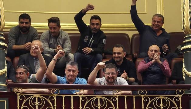 Un grupo de estibadores saludan desde la tribuna de invitados del Congreso tras el debate del real decreto ley de reforma de la estiba.