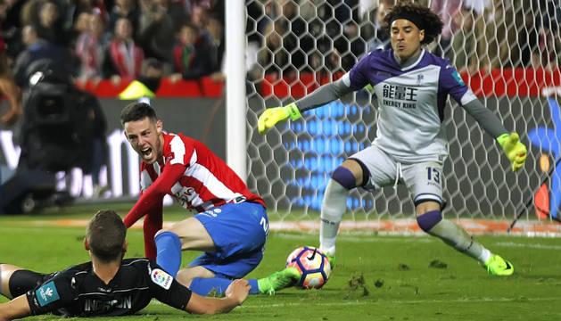 El defensa  Sverrir Ingi Ingason (i) comete penalti sobre Burgui (c), delantero del Sporting de Gijón