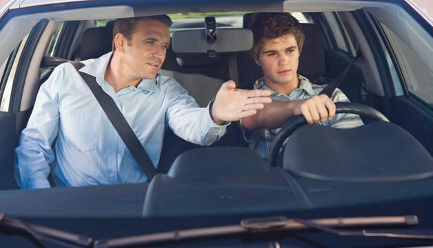 Un profesor de autoescuela imparte directrices de conducción a un alumno dentro de un coche.