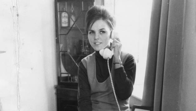 Una mujer conversa a través de un teléfono fijo. Imagen de mediados de los años 60.