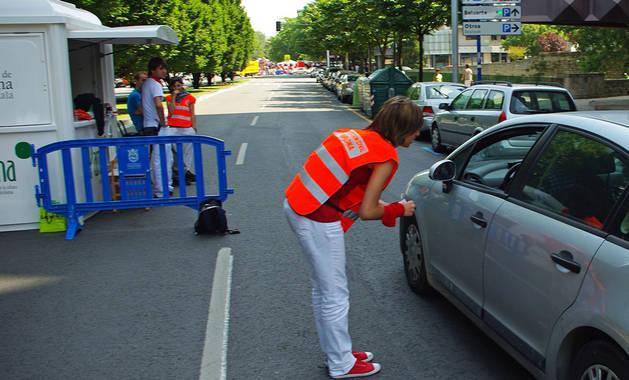 Una joven 'naranjito' da indicaciones a un conductor durante las fiestas de San Fermín de 2010.