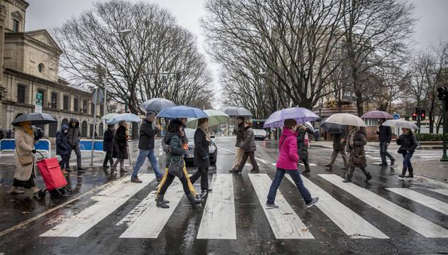 Transeúntes cruzan un paso de cebra de la Cuesta de San Lorenzo, en un día lluvioso.