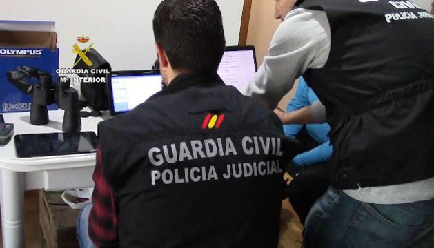 Un agente de Guardia Civil estudia los archivos aprehendidos