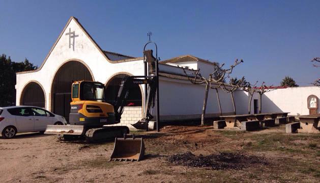 Obras en el exterior de la ermita donde se van a colocar tres nuevos bancos y la canalización del agua.