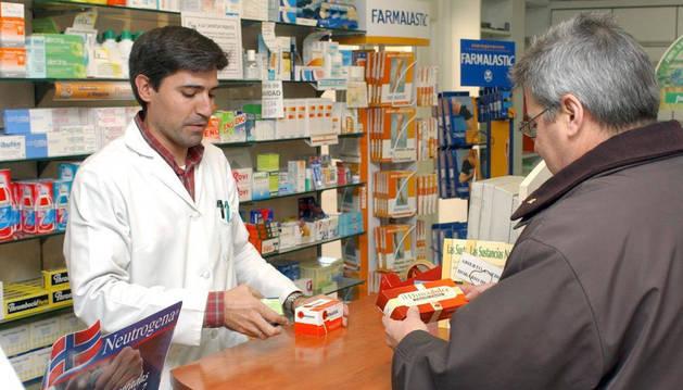 Imagen de un farmacéutico dispensando unos medicamentos a un cliente.