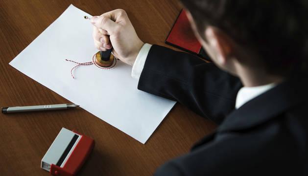 Imagen de un abogado sellando un documento.