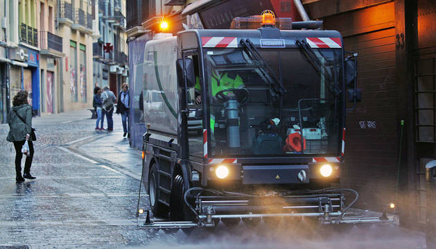 Imagen de una máquina del servicio de limpieza riega la calzada de la calle Mercaderes de Pamplona.