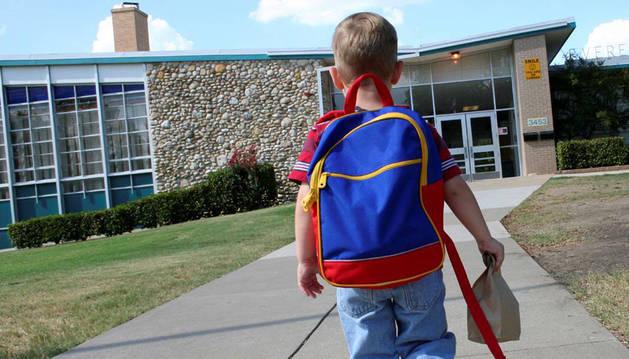 Un niño entra solo en un colegio.