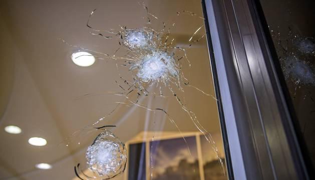 Foto de los agujeros de bala en el escaparate del número 102 de la avenida de los Campos Elíseos de París (Francia).
