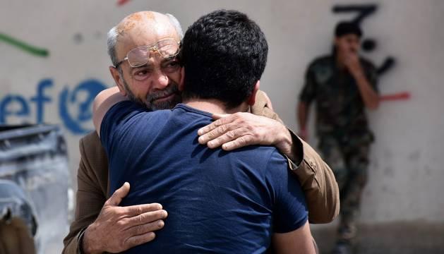 Dos sirios se abrazan entre sollozos